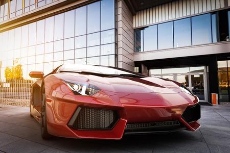 Red fast sports car in modern urban setting. Generic, brandless design. 3D rendering Foto de archivo