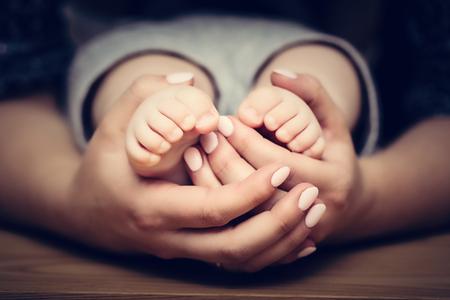 caja fuerte: Pequeños pies del bebé en manos de la madre. Concepto de cuidado de niños, la sensación de seguridad, proteger.