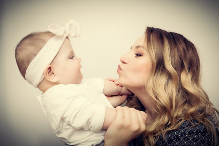 motherhood: Happy moments. Mother holding and playing with her baby. Motherhood, maternity love concept. Vintage