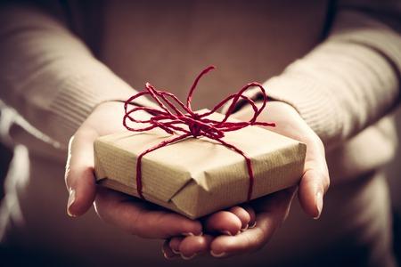Geben ein Geschenk, handgefertigt in Papier eingewickelt. Weihnachtszeit, Jahrgang Stimmung. Standard-Bild - 64703129