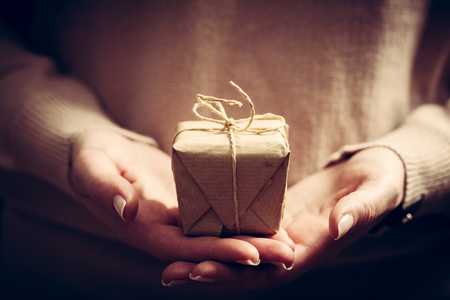 christmas present: Giving a gift, handmade present wrapped in paper. Christmas time, vintage mood.