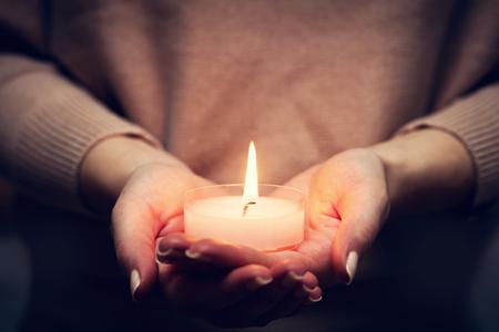 luz de velas: brillante luz de las velas en manos de la mujer. Rezar, fe, religión concepto.