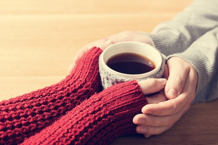 tea cosy: A couple in love warming hands with a hot mug of tea. Wearing cosy woollen jumpers. Stock Photo