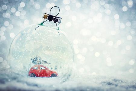 De bal van het Kerstmisglas in sneeuw met miniatuurwinterwereld binnen - auto met Kerstboom, bergen. Glitter achtergrond.