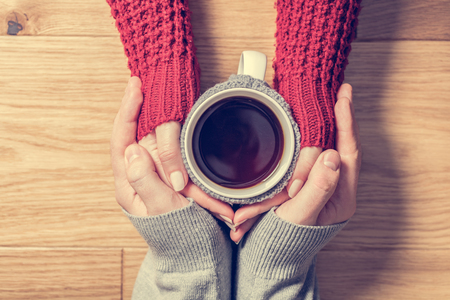 cosy: A couple in love warming hands with a hot mug of tea. Wearing cosy woollen jumpers. Stock Photo