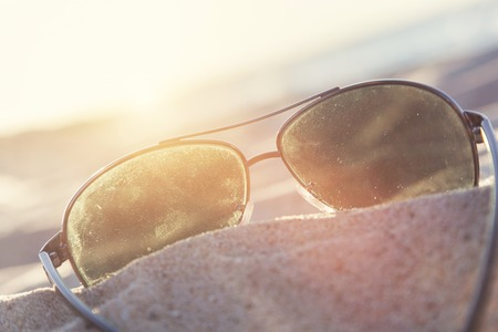 ray ban: Sunglasses on sand at sunset, beach and ocean in the background. Vacation theme.
