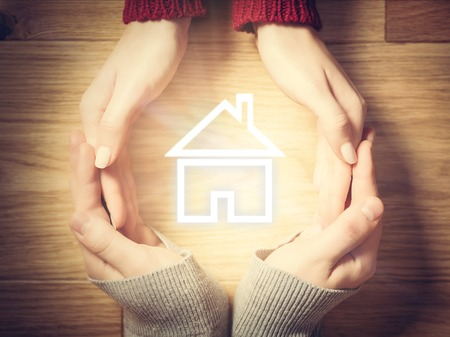 protection hands: House symbol inside hands circle. Concept of home insurance, real estate protection, mortgage loan etc. Stock Photo