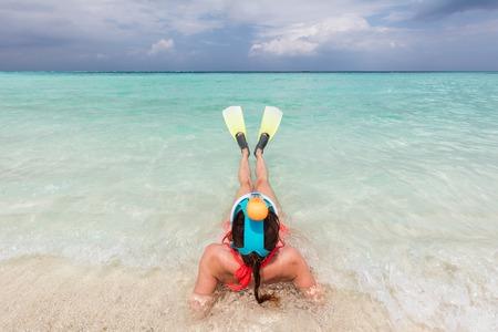 flippers: Mujer con máscara de buceo y aletas listo para bucear en el océano, Maldivas. agua turquesa claro.