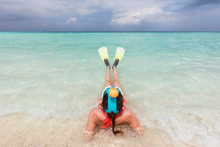 scuba goggles: Woman wearing snorkeling mask and fins ready to snorkel in the ocean, Maldives. Clear turquoise water. Stock Photo