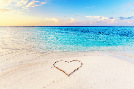 Heart drawn on sand of a tropical beach at sunset. Clear turquoise ocean. Maldives islands.