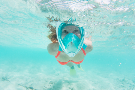 Woman snorkeling underwater in Indian Ocean, Maldives. Clear turquoise water.