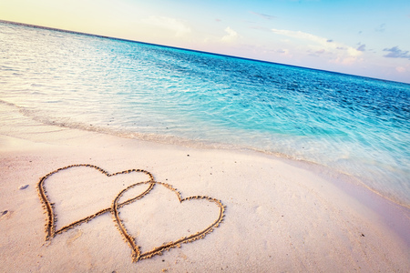 Two hearts drawn on sand of a tropical beach at sunset. Clear turquoise ocean. Maldives islands. Standard-Bild