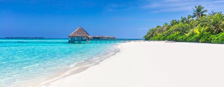 Panorama di ampia spiaggia di sabbia su un'isola tropicale nelle Maldive. Palme da cocco e water lodge sull'Oceano Indiano.
