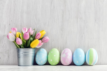 Easter eggs and a spring bouquet of tulips on a wooden table. Springtime decoration. 스톡 콘텐츠