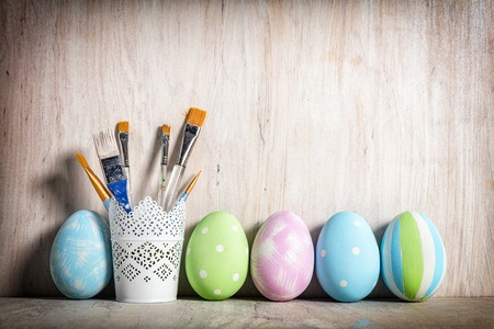 Pastel Easter eggs and brushes in a rustic cup on wooden desk.