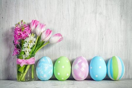 イースターエッグと木製のテーブルにチューリップの春の花束。春の装飾。