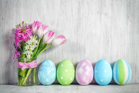 spring holiday: Easter eggs and a spring bouquet of tulips on a wooden table. Springtime decoration. Stock Photo
