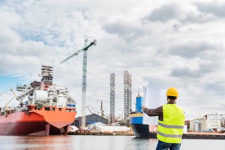 Scheepsbouwwerktuigkundige die documenten en plannen van bouw in de haven in een haven controleert. Het dragen van veiligheidshelm en geel vest, gevouwen papieren vasthouden. Stockfoto
