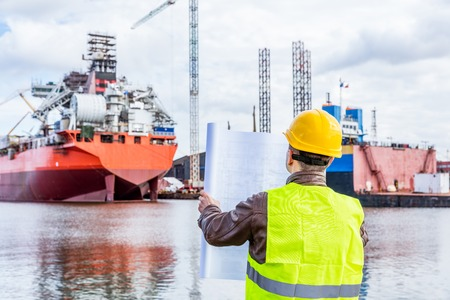 dockside: Shipbuilding engineer checking documents and plans of construction at the dockside in a port. Wearing safety helmet and yellow vest, holding folded papers. Stock Photo
