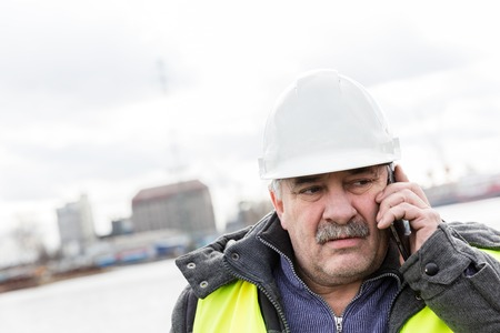 shipbuilding: Senior engineer builder talking on the phone at the construction site in a port. Wearing safety helmet and yellow vest.
