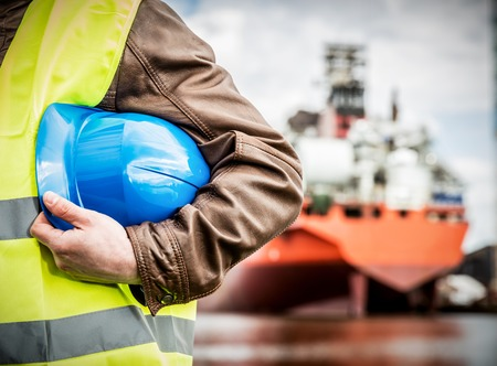 dockside: Shipbuilding engineer stands at the dockside in a port. Man is holding a safety helmet, close-up.. Shipbuilding industry