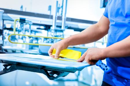 L'homme préparation de matériel pour la sérigraphie dans un atelier. industrie Serigraphy. Fabrication travail. Banque d'images - 75014950