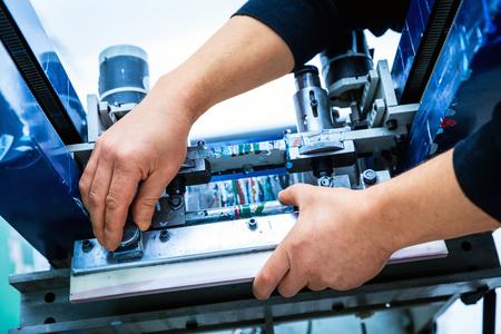 work worker: Worker preparing print screening metal machine. Industrial printer. Manufacture work.
