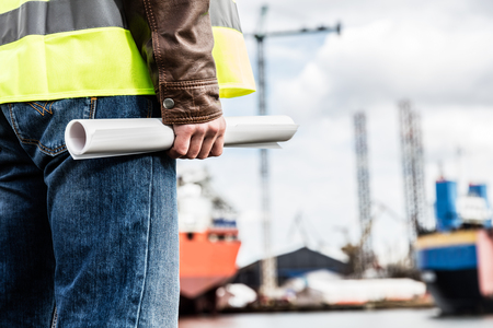 dockside: Shipbuilding engineer stands at the dockside in a port. Man is holding construction documents. Shipbuilding industry