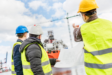 Shipbuilding engineers introducing new solution in a shipyard. All men wearing safety helmets and yellow vests. Transport industry. Stock Photo