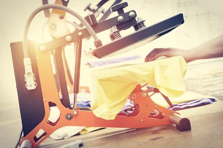 실크 스크린 인쇄 기계에서 인쇄하기 위해 t- 셔츠를 준비하는 사람