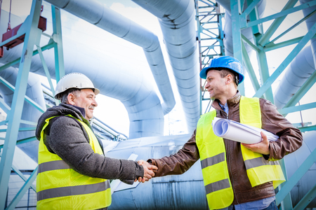 Oil refinery engineers handshake. Petrochemical and gas industry successful deal. Cooperation concept.