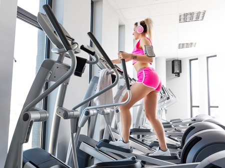 Young woman training at crosstrainer in a modern gym. Cardio exercises and workout. Sport and healthy lifestyle.
