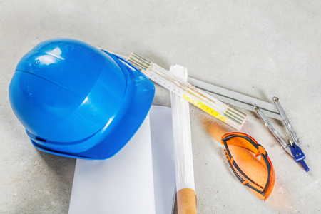 service broker: Hard hat, safety glasses and blueprints at the construction site. Building and engineereing tools close up.