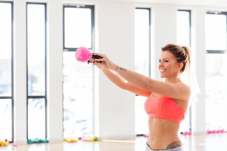 Cheerful, fit woman doing a kettlebell swing exercise. Body weight and fitness workout concept.