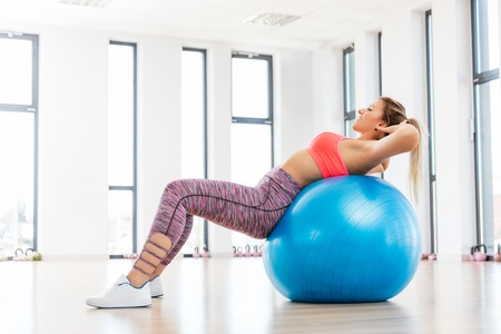 fitball: Young woman training with fitball at the fitness club. Fatburning and body shaping concept.