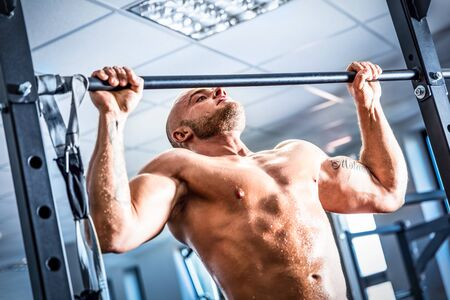 traction: Muscular strong man training at a gym. Crossfit chinup training. Bodybuilding and fatburning.