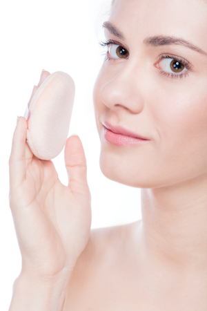 clarifying: Young beautiful woman applying powder on her skin. Make-up and skin care
