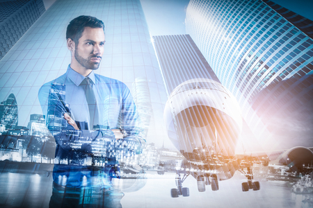 Young businessman thinking. Double exposure city downtown and airplane background. Smart business, travel concept Stock Photo