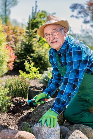 Senior gardener digging in a garden. Preparing soil for a new plant. Gardening concept.
