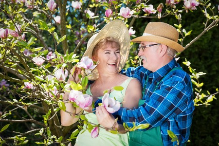 Mature couple in sunhats embracing in garden, hugging and smiling. Looking at beautiful magnolia flowers. Family time outdoors. Active retirement.