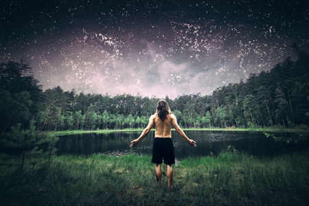 Young man standing in the forest with arms wide open. Inspirational view of a summer night sky full of stars, lake and woods. Nature and freedom concept.
