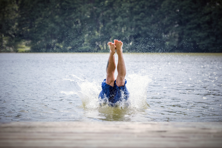 careless: Young man diving into a lake. Careless and risky water jump. Summer vacation dangerous outdoor activity.
