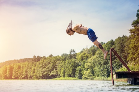 Young fit man jumping into a lake from a wooden jetty. Water sport. Side view. Stock Photo