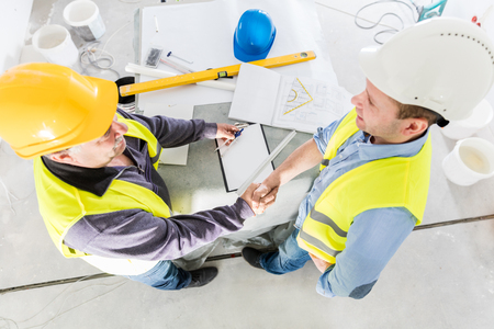 construction project: Architect and construction engineer handshake. Successful building experts meeting. Real estate market. Top view.