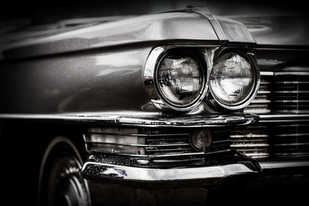 Close up detail of restored classic American car. Focus on headlights. Retro vehicle in black and white. Stock Photo