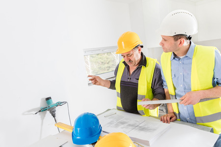 construction project: Architect and construction engineer indoor meeting. Building experts cooperation and project analysis. Real estate market.
