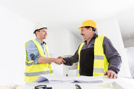 construction project: Architect and construction engineer handshake. Successful building experts meeting. Real estate market. Stock Photo