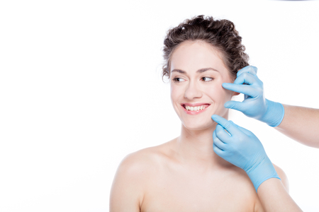 Smiling woman having skin checkup before plastic surgery. Face correction concept.
