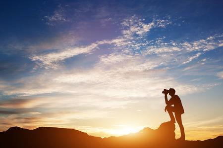 Homme debout sur les rochers, regardant à travers les jumelles. Regard vers l'avenir. Ciel scénique du coucher du soleil. Illustration 3D