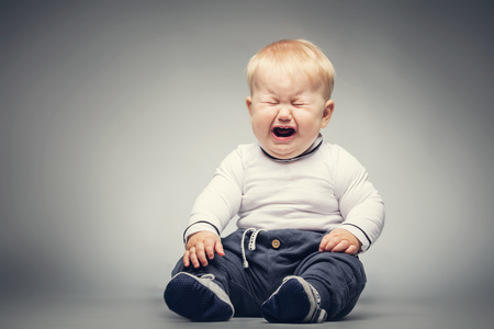 작은 아기 얼굴 표정으로 바닥에 앉아. 스톡 콘텐츠
